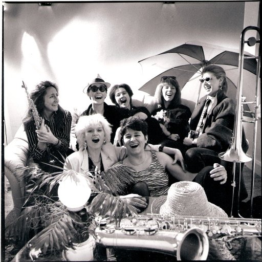 A black and white publicity shot of Hi Jinx, posing in a tropical setting. The seven women are sitting close together on a sofa, some with arms around each other, laughing and grinning, under bright lights, with a huge beach umbrella, straw hats, palm tree branches, saxophones and a trombone.