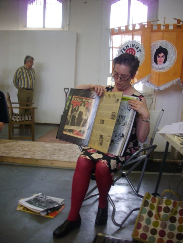 Lucy Whitman shares the contents of her scrapbook which includes the publications Jolt and Drastic Measures. She holds the pages of the scrapbook open and talks about them. In the background a visitor to the exhibition, and a WLM symbol on the Feminist Disco banner.