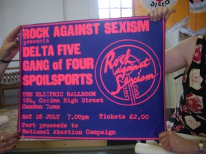 Bright blue poster with day glo pink writing. 'Rock Against Sexism present Delta 5, Gang of Four, The Spoilsports. Electric Ballroom, Camden. Admission £2. Part proceeds to National Abortion Campaign.' The RAS logo is on one side, pink, the name written over a symbol which combines a guitar fretboard with a women's symbol. The poster is being held up to be photographed during a presentation by Lucy.