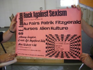 Poster from Lucy Whitman's collection of Rock Against Sexism memorabilia held up and photographed during a presentation. Pink background, black writing says 'Rock Against Sexism, South East London, benefit for Gay Pride 1980. The Au Pairs, Patrik Fitzgerald, Nurses, Alien culture. At the Albany Empire, SE8. 23 June. £2/1.50.'