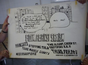 A hand-drawn poster with drawings of buildings in the background, for a RAS event at the Albany Empire, Deptford, London SE8. The Raincoats, Necessary Evil and Young Monster Giants. £2/1.50.'