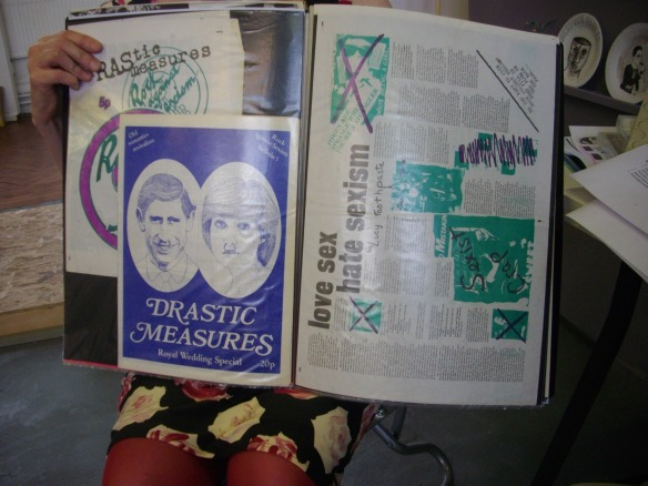 Lucy Whitman's scrapbook, displayed open here, shows 2 of the covers of the Rock Against Sexism magazine Drastic Measures. One is a 'Royal Wedding Special,' with drawings of Prince Charles and Lady Di wearing nose rings. Another page is not legible in this photo, except for a headline 'love sex, hate sexism.'