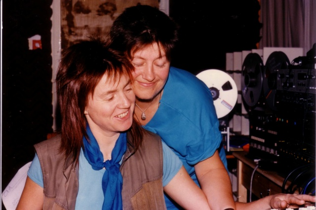 Colour photo of Rosemary and Jana in the Ova music studio surrounded by equipment. Jana looks over Rosemary's shoulder and the two smile happily.