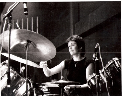 Close up of Jackie Crew behind her drum kit, playing cymbal and snare drum.