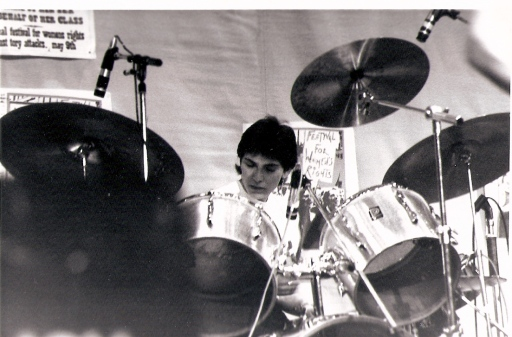 Jackie is shown in this black and white photo playing her drum kit intently, her face just visible above tom toms, 3 cymbals and microphones. A partly visible poster says ' festival for women's rights, against Tory attacks.'