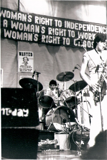 Jackie, Jam Today's drummer, and Julia, saxophonist, playing intently. A large banner above the stage reads 'A WOMAN'S RIGHT TO INDEPENDENCE, A WOMAN'S RIGHT TO WORK, A WOMAN'S RIGHT TO CHOOSE.' Behind the drum kit is a 'WANTED' poster bearing Thatcher's face.