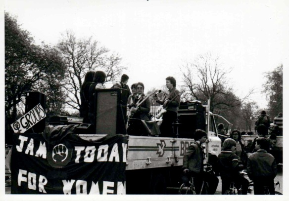 Band members on an open top lorry, with a banner on the back 'Jam Today for women.' Hyde Park can be seen in background, and kids alongside.