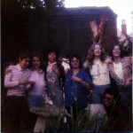 Seven Jam Today members in a colour photo taken in the garden of rehearsal shed, during a break, smiling, some with arms around each other.
