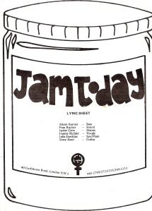 A small white booklet of lyrics bearing the Jam Today logo of a black and white drawing of a jam jar and a WLM symbol of a women's symbol and clenched fist, and the list of band members.