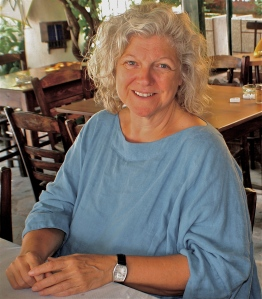 A colour photo of smiling, relaxed Jan seated in a cafe in Greece.