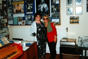 A colour photo of Jen Wilson with her arm around the shoulder of drummer Crissy Lee, both smiling, in the archive, surrounded by records, photos and posters from the collection, plus desk and piano.