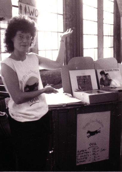 Ova administrator Jenny Gibbs, wearing an Ova tee shirt, sells records at a show. Black and white photo in which she gestures toward a table bearing piles of Ova records.