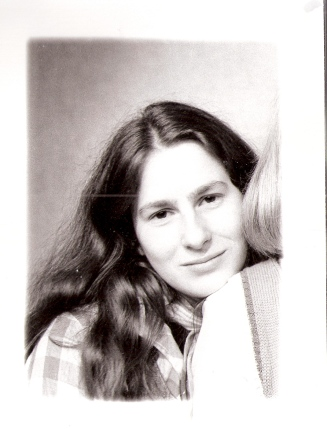 Black and white portrait of Jo Richler when young, with centre-parted long hair in a classic 70s style.