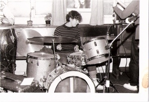 Josefina in rehearsal with the Guest Stars, seated at her drum kit and focusing seriously on playing.