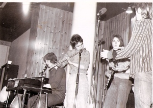 Four members of Jam Today on stage, looking up from the audience's point of view. Keyboard, flute and guitar players and the singer playing tambourine looking at the guitarist. Amplifiers in background, microphones in front.