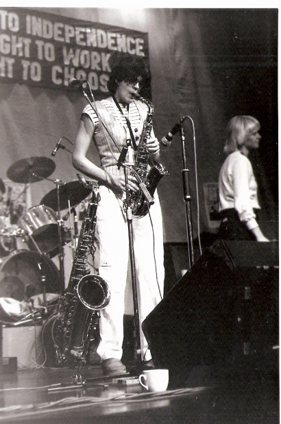 Julia is playing the saxophone and Barbara singing, into microphones at the front of the stage, and Jackie's drum kit is visible behind them. A large banner above the stage reads 'A WOMAN'S RIGHT TO INDEPENDENCE, A WOMAN'S RIGHT TO WORK, A WOMAN'S RIGHT TO CHOOSE.'