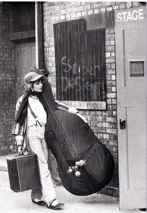 An iconic black and white photo of Julia approaching a Stage Door, carrying her double bass in its cover with one arm and an amplifier in her other hand. Used in posters for the Women Live festival.