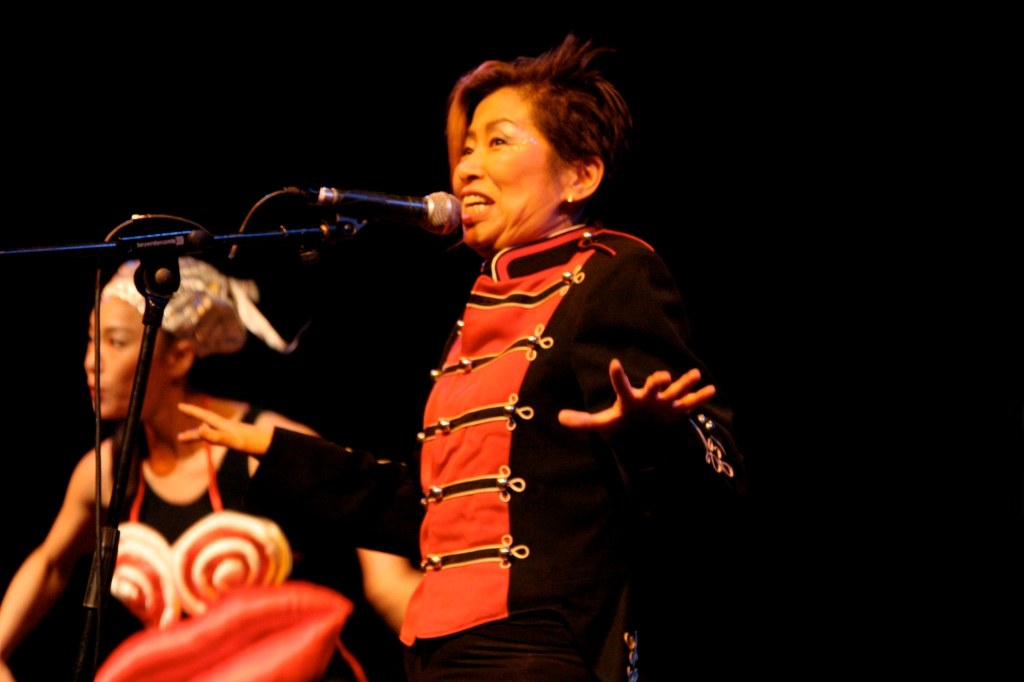 Colour photo of Frank Chickens performing. The group wears bright and dramatic costumes. Here Kazuko sings into a microphone, dressed in an orange military-style jacket. Another woman is beside her wearing props of exaggerated breasts and lips.