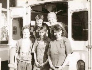 The Fabulous Dirt Sisters stand outside their van, 'nee-naw.' Black and white photo. Smiling.