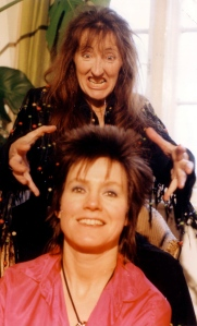 Lazy Country publicity colour shot, Rosemary in front is smiling while Dee behind her grimaces and pretends to grab her head.