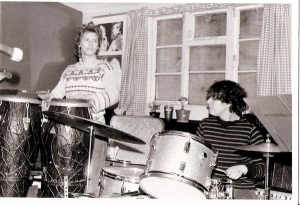 Linda, standing behind two conga drums, and Josefina, seated at her drum kit, playing together in rehearsal.