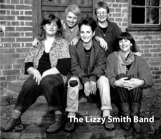 Five women from the Lizzy Smith Band sitting on steps outdoors, in a publicity shot for the band.