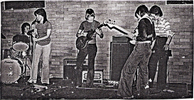 Five women in rehearsal in a university hall. Drummer, vocalist, guitarist, bassist, keyboards, all looking serious. Amplifiers in background.