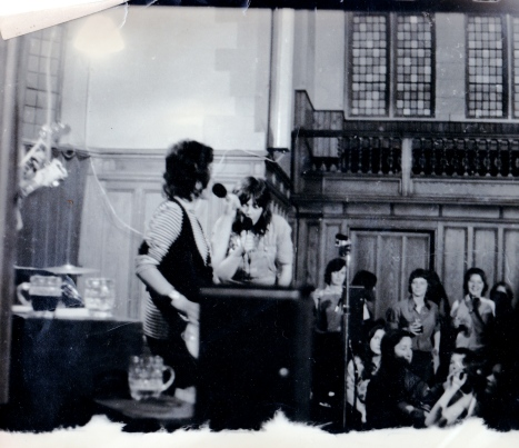 A second photo of Luchia and Angela on stage, singing, with women audience members watching from the side of the hall.