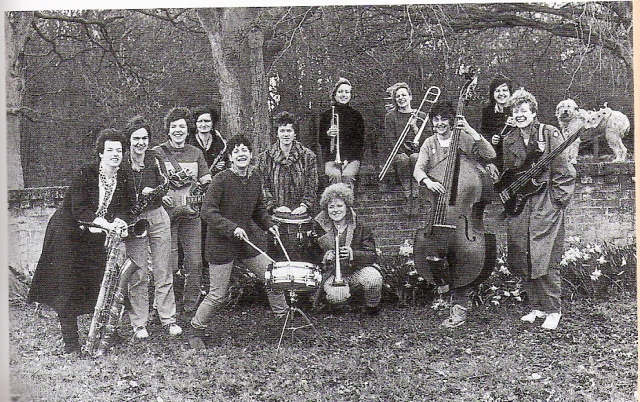 In a black and white publicity shot, thirteen women from the band, and a dog, stand outside in a walled garden with their instruments, laughing.