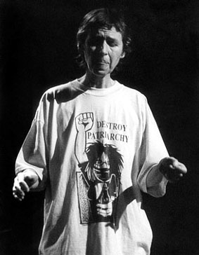 Black and white photograph of Maggie Nicols singing, focusing with eyes closed and hands outstretched expressively, wearing a t-shirt with a cartoon of a spiky-haired girl raising a large clenched fist and the words 'Destroy Patriarchy.'