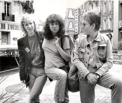 Black and white photo of Maggie Nicols, Lindsay Cooper, Irene Schweizer (head tilted to look at Maggie and Lindsay). A background of French city streets.