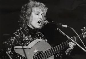 Black and white image of Maria Tolly singing into a microphone, playing an acoustic guitar.