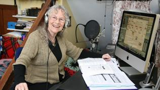 Colour image of Maria recording music using a computer. Big smile.