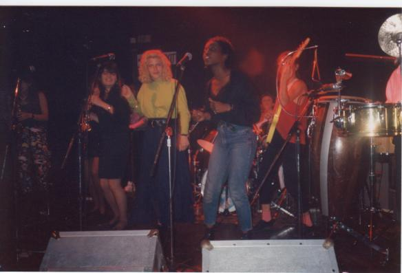A dynamic picture of several women of Meet Your Feet on stage in performance, singing and playing electric bass guitar and guitar.