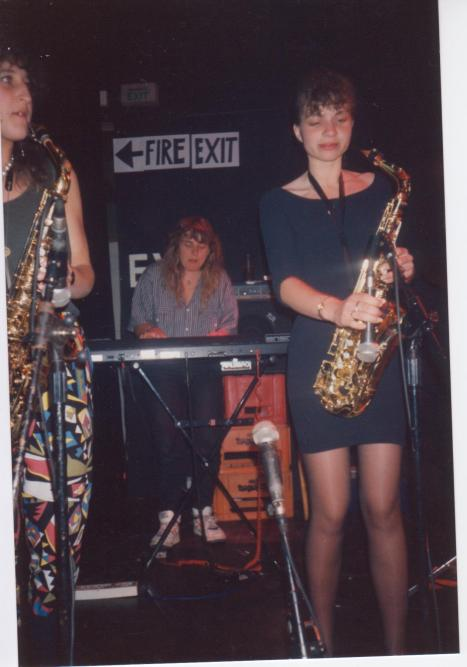 Photo of two saxophone players and keyboard player performing on stage.