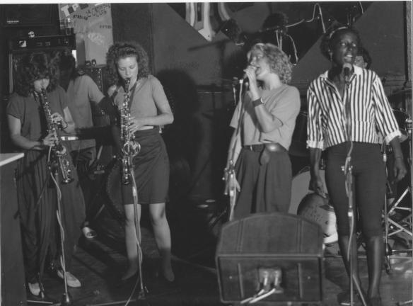 Photo of the band performing in a pub showing sax and clarinet players, singers and drum kit, amplifiers and microphones.