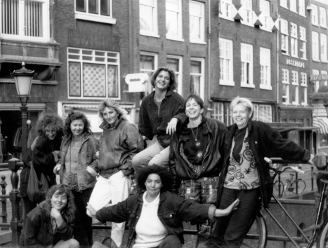 The nine women of Meet Your Feet posing on a bridge in Amsterdam smiling and excited.
