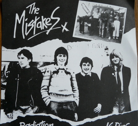 Cover for 'Radiation.' Black and white image of band with handwritten 'The Mistakes' x