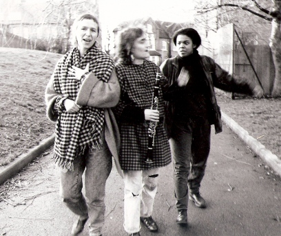 The three members of No Rules OK in a black and white shot, walking along a fortpath talking animatedly and smiling. Shirli holds a clarinet.