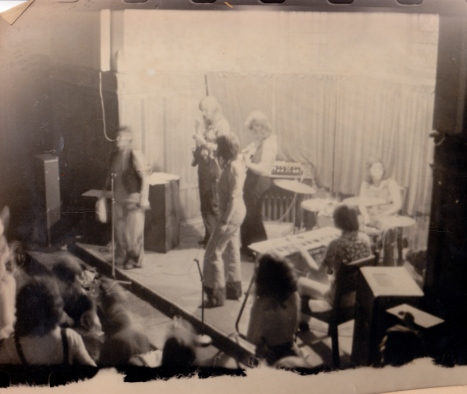 A tattered photo of the band on stage at the Edinburgh conference taken from above shows them all playing and some of the audience watching and dancing.