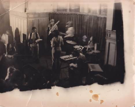 The whole band is seen on stage from above, in a very tattered photo complete with coffee stains. Some women in the audience are dancing.