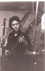 Patsy playing bass guitar at a gig, microphones visible.