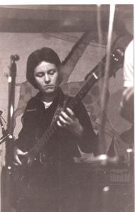 Patsy playing bass guitar at a gig, microphones visible.