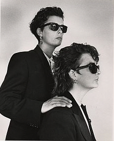 A posed publicity shot of the two Pearl Divers wearing dark sunglasses, black suits and solemn expressions, gazing into the distance. Lou seated, Vick with a hand on her shoulder.