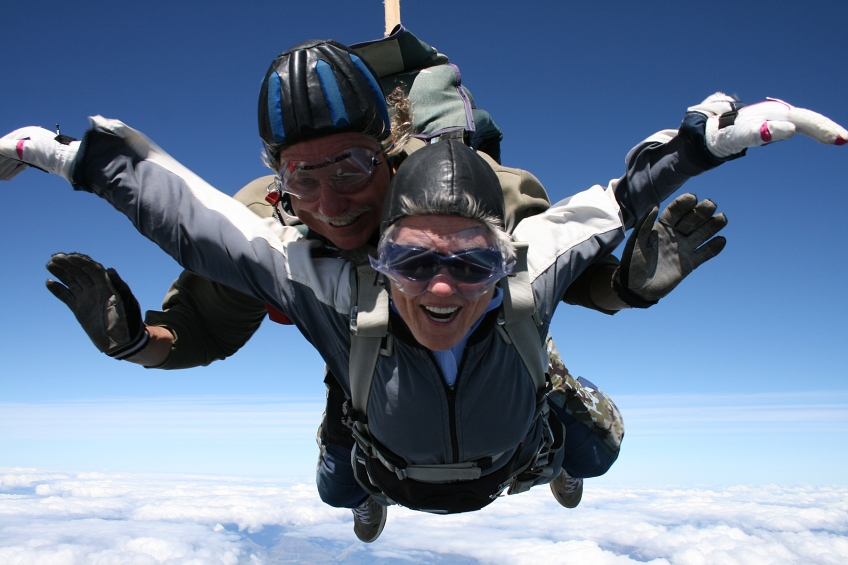 Bright Picture of Peggy skydiving, arms spread against the sky, smiling and floating.