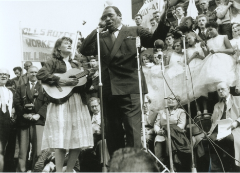 Peggy on the plinth in Trafalgar Square in 1960, playing the guitar next to Paul Robeson who is singing, one hand over his ear. Crowds and placards in background, but protest unknown.