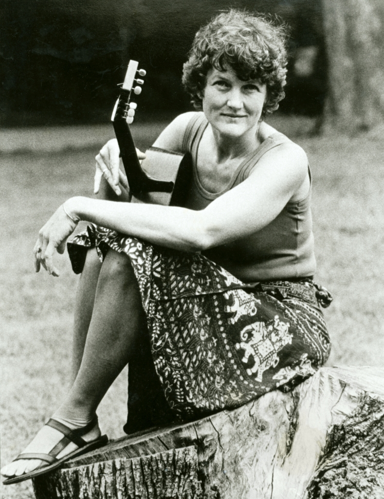 A 1971 publicity shot of Peggy seated, smiling and holding acoustic guitar.