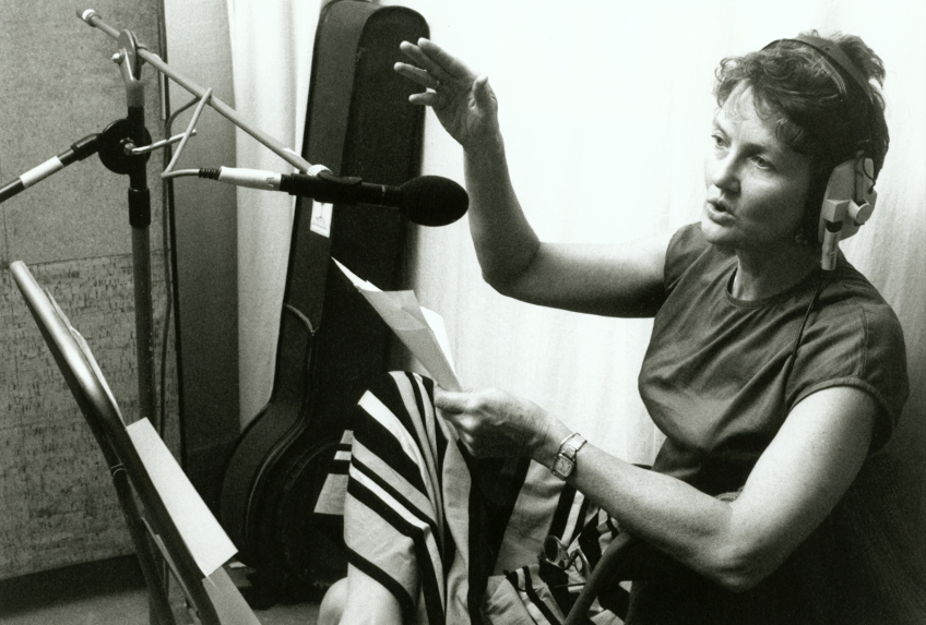 Peggy in recording studio, singing into a micrphone, guitar case in background and music sheet on her knee.