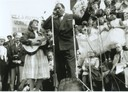 Peggy plays guitar and sings on stage with Paul Robeson in Trafalgar Square. Placards and crowds in the background but not clear what the demonstration is.