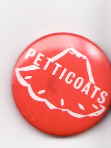 A pink badge with 'Petticoats' written in white letters, over a drawing of the outline of a flared petticoat.